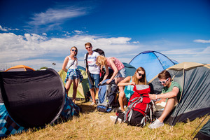Group of teenage boys and girls at summer music festival, sitting on the ground in front of tents, packing