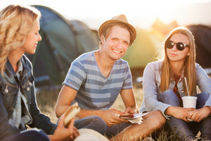 Group of teenage boys and girls at summer music festival, sitting on the ground in front of tents, resting and eating