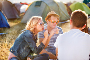 Group of teenage boys and girls at summer music festival, sitting on the ground in front of tents resting and eating