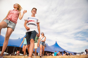 Group of teenage boys and girls at summer music festival walking in front of big blue tent, sunny day