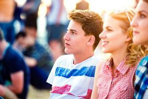 Group of teenage boys and girls enjoying summer music festival, sitting on the ground