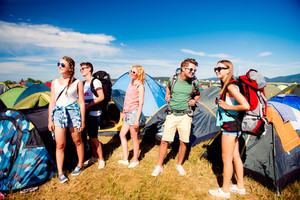 Group of teenage boys and girls with backpacks at summer music festival, in front of tents