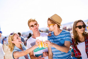 Group of teenage boys and girls with beers in a crowd at summer music festival, , sunny day