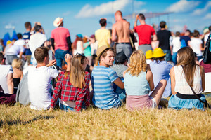 Group of teenagers at summer music festival, sitting on the grass, back view, rear, viewpoint