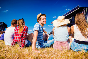 Group of teenagers at summer music festival, sitting on the grass in front of stage, back view, rear, viewpoint