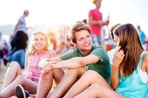 Group of teenagers at summer music festival, sitting on the ground , hipster boy in green t-shirt