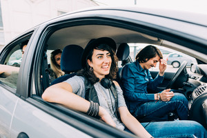 Group of young beautiful multiethnic man and woman inside a car traveling - holiday, journey, traveler concept