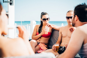 Group of young beautiful multiethnic woman and man friends sitting in a bar on the beach something to drink and chatting - friendship, relaxing concept