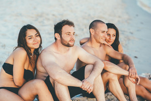 Group of young beautiful multiethnic woman and man friends sunbathing on the beach in summertime, looking over smiling - friendship, relaxing concept
