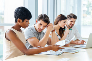 Group of young business people sitting and talking in office