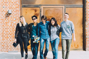 Group of young handsome multiethnic woman and man ealking outdoor in the city, hugging, smiling and having fun - happiness, friendship, together concept