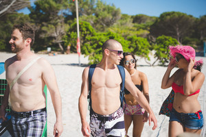 group of young multiethnic friendgroup of young multiethnic frs women and men at the beach in summertime walking