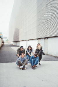 Group of young multiethnic friends having fun laughing, and smiling, racing sitting on their skateboard - friendship, fun concept