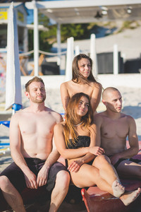 Group of young multiethnic friends seated on paddle boat in swimsuit looking at the horizon at the beach at sunset - future, relax, friendship concept