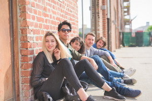 Group of young multiethnic friends seated on the floor leaning against a brick wall with a skateboard, looking in camera smiling - friendship, sport concept