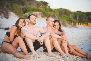 Group of young multiethnic friends seated on the foreshore in swimsuit looking at the horizon at the beach at sunset - future, relax, friendship concept