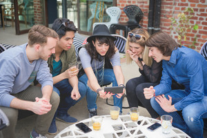 Group of young multiethnic friends sitting in a bar chatting to each other having fun using smartphone taking selfie - social network,technology, communication, technology concept