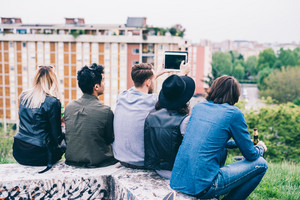 Group of young multiethnic friends sitting in a park, seen from behind, looking at the horizon taking selfie - future, prospective, friendship concept