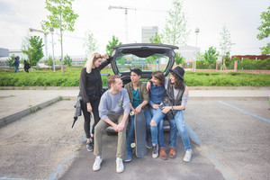 Group of young multiethnic friends sitting in a trunk of a car, talking to each other, having fun - friendship, relax concept