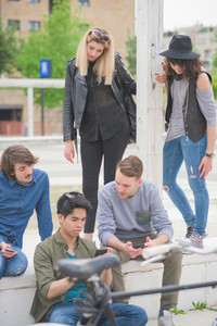 Group of young multiethnic friends sitting on a small wall talking to each other, using a smartphone, having fun - friendship, relaxing concept