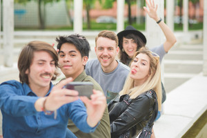 Group of young multiethnic friends sitting on a small wall, talking to each other, using a smartphone, taking a selfie , having fun - friendship, relaxing concept