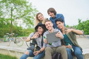 Group of young multiethnic friends sitting on a small wall using a smartphone, having fun taking a selfie, drinking a beer - friendship, relaxing concept