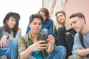 Group of young multiethnic friends sitting on a staircase talking to each other, using a smartphone, having fun - friendship, relaxing concept