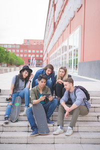 Group of young multiethnic friends sitting on a staircase with skateboard, talking to each other, using a smartphone, having fun - friendship, relaxing concept