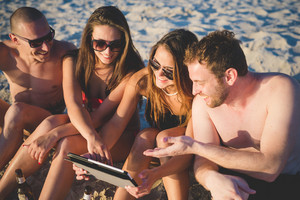 Group of young multiethnic friends with digital tablet sitting at the beach taking a selfie -  multi cultural friendship and social media networking concepts - Interacting with technological devices