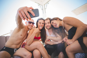 group of young multiethnic friends women and men at the beach bar in summertime using smartphone taking selfie
