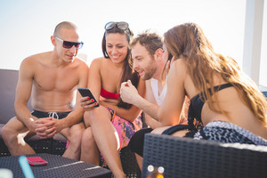 group of young multiethnic friends women and men at the beach bar in summertime using smartphone