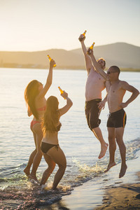 group of young multiethnic friends women and men at the beach in summertime drinking beer jumping and dancing