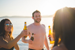 group of young multiethnic friends women and men at the beach in summertime drinking some beers on the foreshore - friendship, relaxing, happy hour concepts