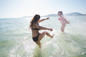 group of young multiethnic friends women and men at the beach in summertime having fun in the water splashing