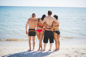 group of young multiethnic friends women and men at the beach in summertime hugging back watching sea- teamwork, friendship, relax concept