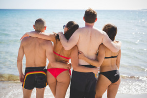 group of young multiethnic friends women and men at the beach in summertime hugging back watching sea