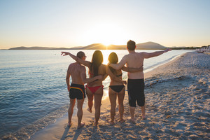 group of young multiethnic friends women and men at the beach in summertime hugging back watching sunset