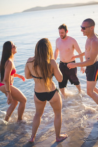 group of young multiethnic friends women and men at the beach in summertime jumping and dancing