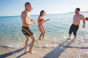 group of young multiethnic friends women and men at the beach in summertime jumping on the water
