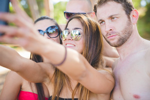 group of young multiethnic friends women and men at the beach in summertime making selfie