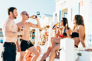 group of young multiethnic friends women and men at the beach in summertime outside a bar, having a beer - relaxing, friendship, having fun concept