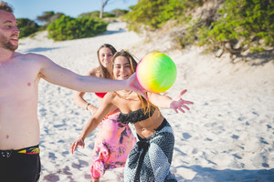 group of young multiethnic friends women and men at the beach in summertime playing with ball  sport, relax, fun concept