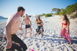 group of young multiethnic friends women and men at the beach in summertime playing with ball