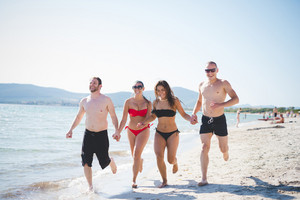 group of young multiethnic friends women and men at the beach in summertime running hand to hand