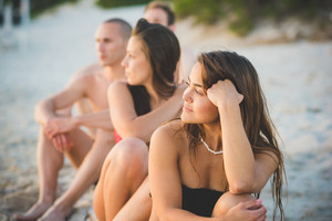 group of young multiethnic friends women and men at the beach in summertime sitting sand watching sunset
