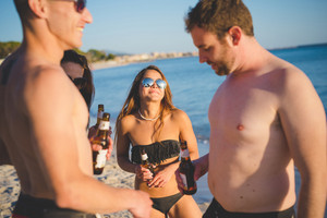 group of young multiethnic friends women and men at the beach in summertime smiling on the foreshore with some beers in their hands - happy hour, relaxing, friendship concepts