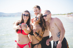 group of young multiethnic friends women and men at the beach in summertime taking selfie in the water