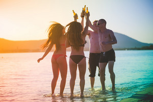 group of young multiethnic friends women and men at the beach in summertime toasting and drinking beer jumping and dancing - friendship, carefreeness concept - colorful filter