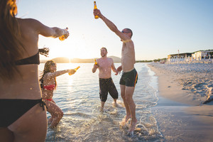 group of young multiethnic friends women and men at the beach in summertime toasting and drinking beer jumping and dancing - friendship, carefreeness concept