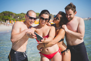 group of young multiethnic friends women and men at the beach  in summertime using smartphone taking selfie - social network, technology, relax concept